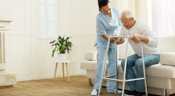 caregiver assisting senior patient in standing