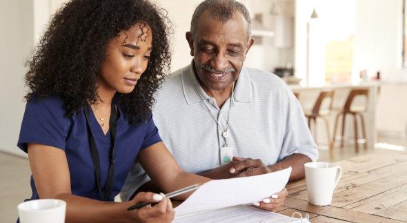 caregiver assisting senior patient in reading
