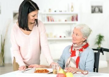 caregiver giving senior woman her meal