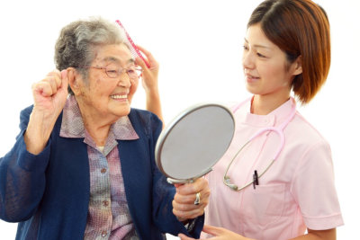 caregiver assisting senior woman smiling