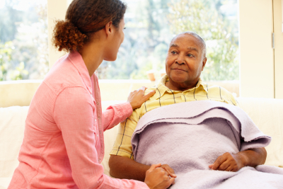 caregiver holding the hand of senior man lying in the bed