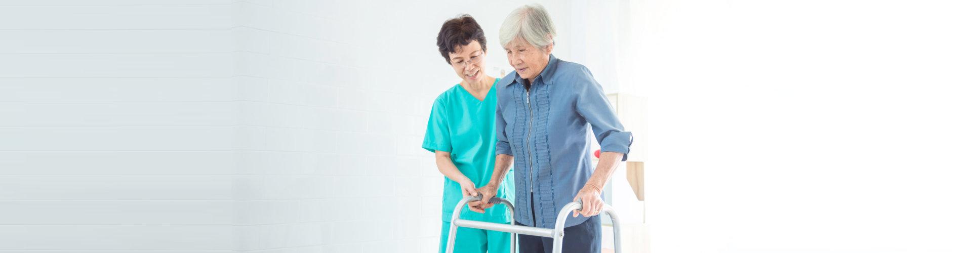 caregiver assisting senior woman walking using her walking frame