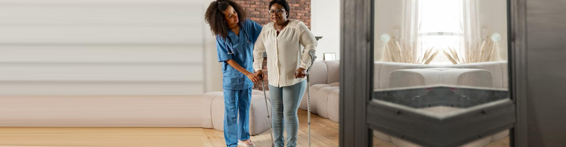 female nurse assisting senior woman walking