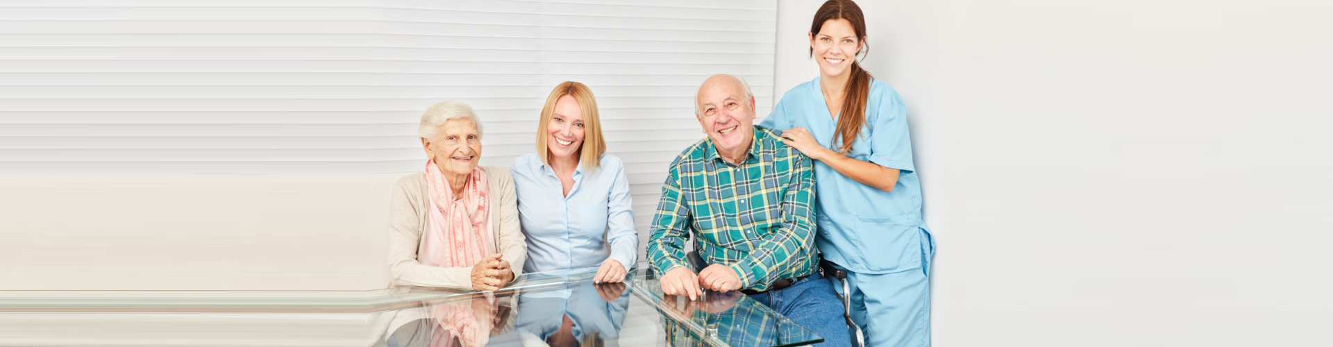 senior couple with adult woman and caregiver smiling